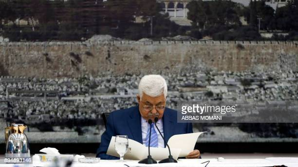 TOPSHOT Palestinian Authority President Mahmud Abbas reads while giving an address in front of a picture of the Dome of the Rock mosque in...