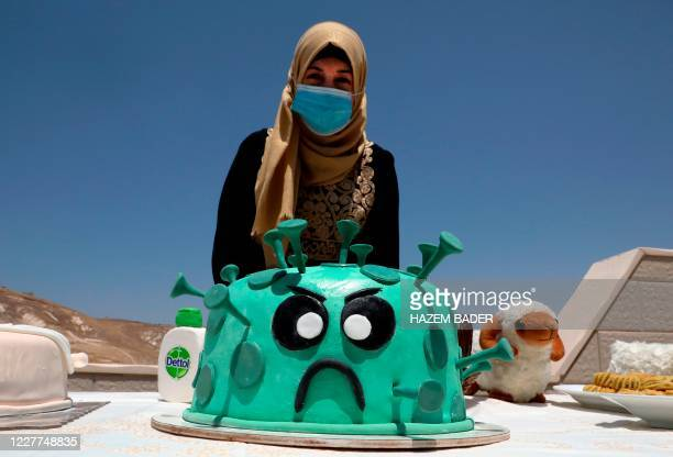 Palestinian baker Nidaa Abu Dheir displays a cake design of the coronavirus on the roof of her home in the village of Dar Salah in the occupied West...