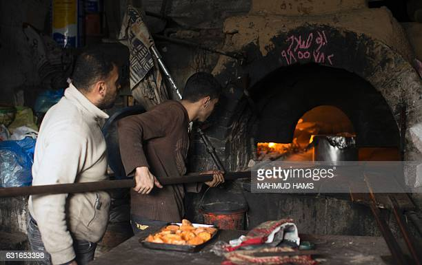 A Palestinian baker places a pot of stew inside traditional wood oven in Gaza City on January 14 2017 Crippling shortages of electricity in Gaza and...