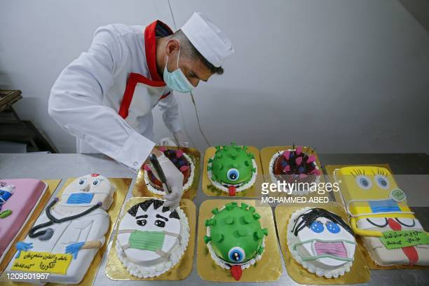 Palestinian baker puts the final touches on coronavirus-themed cakes at his bakery in Khan Yunis in the southern Gaza Strip, on April 8, 2020.