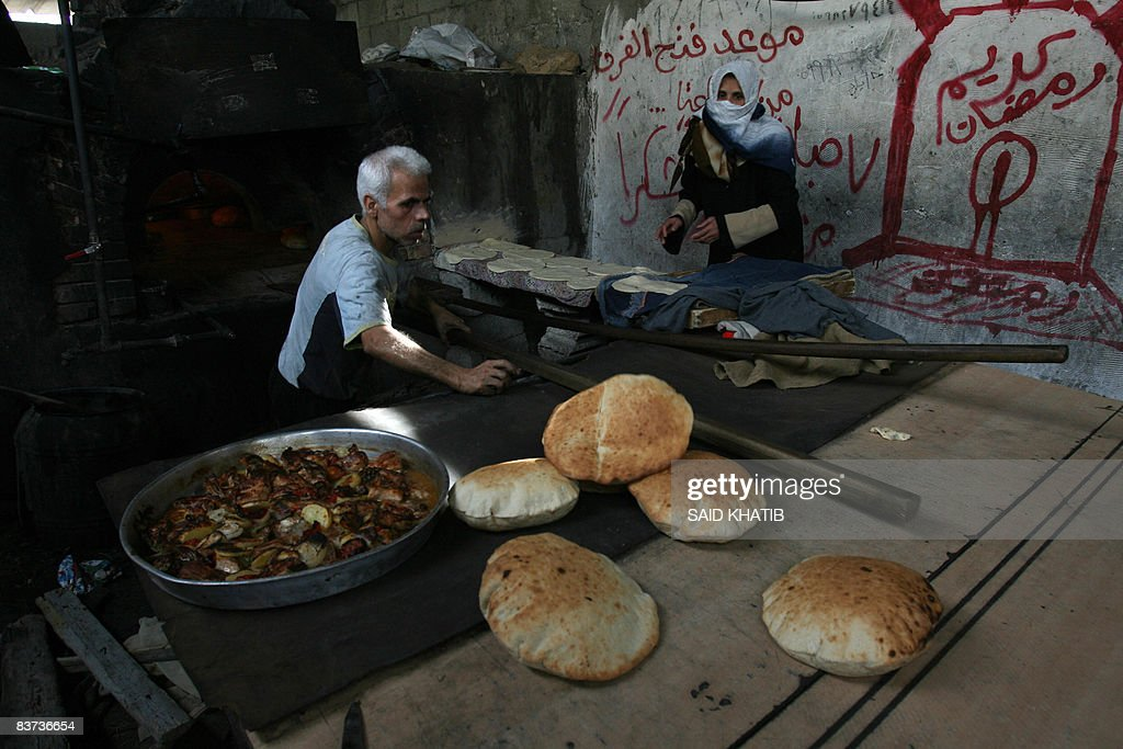 A Palestinian baker removes freshly-bake