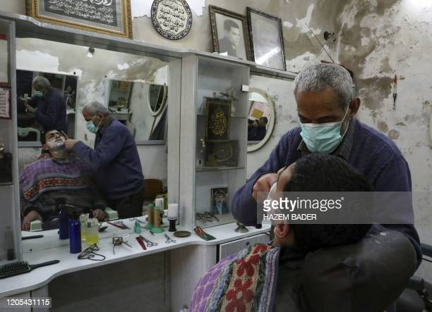 Palestinian barber wearing a mask as a protective measure against the cornonavirus COVID-19, shaves his client at his shop in the occupied West Bank...