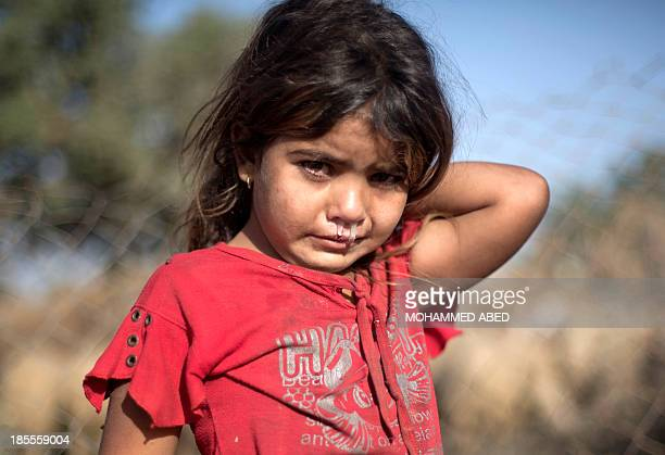 Palestinian Bedouin girl with a snotty nose poses at an encampment where two bedouin families live amid harsh living conditions with no electricity...