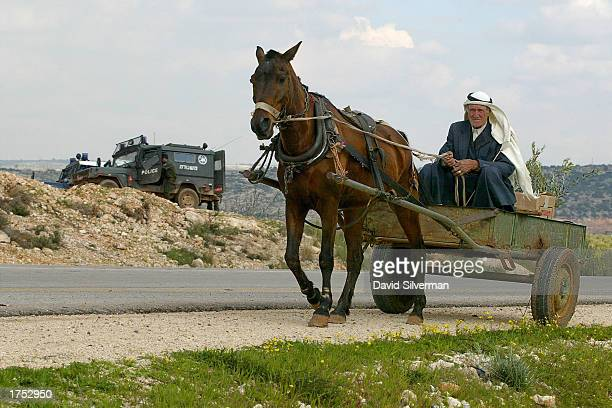 Palestinian Bedouin man rides his horseandcart past an Israeli police patrol January 30 2003 on the outskirts of the West Bank town of Qalqilya Two...