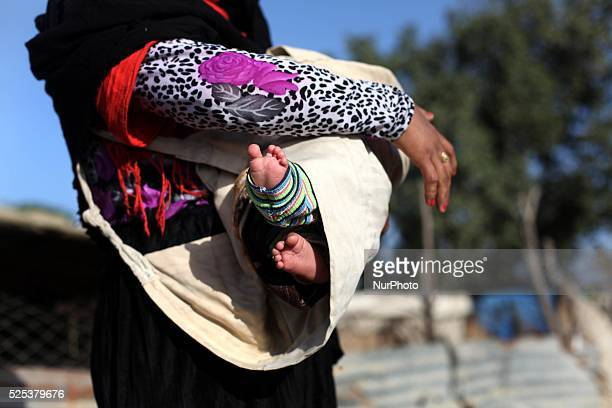 A Palestinian Bedouin woman carries a baby on her back at an encampment where two bedouin families live amid harsh living conditions with no...