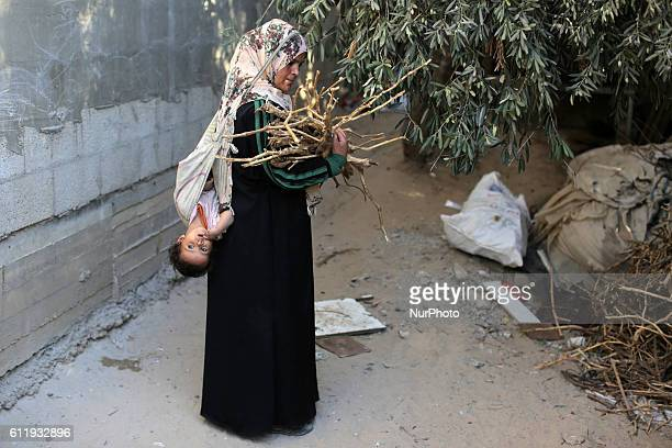 A Palestinian Bedouin woman is carrying her child while collecting firewood outside her house on October 2 2016 in the south of Gaza City