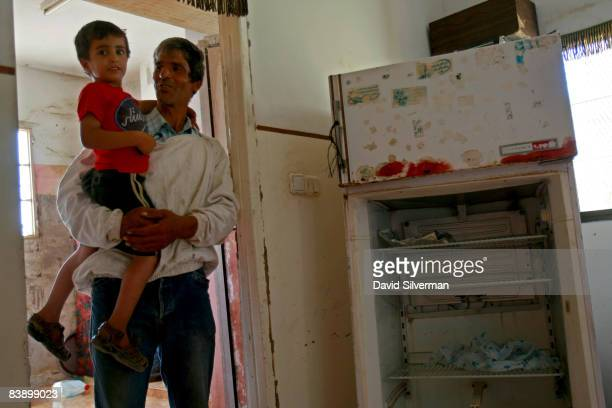 Palestinian beekeeper Muafak Faris Najem who has been unemployed since a work injury a few years ago stands proudly with his youngest son Moeman...