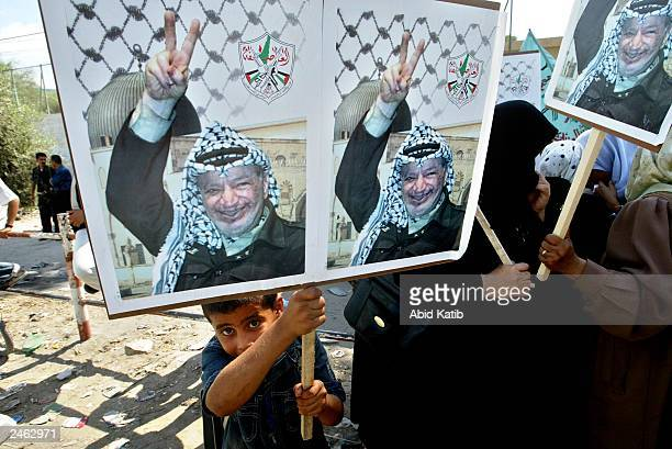 Palestinian boy and women hold posters of Arafat as they attend a rally supporting Palestinian leader Yasser Arafat at Khan Younis refugee camp...