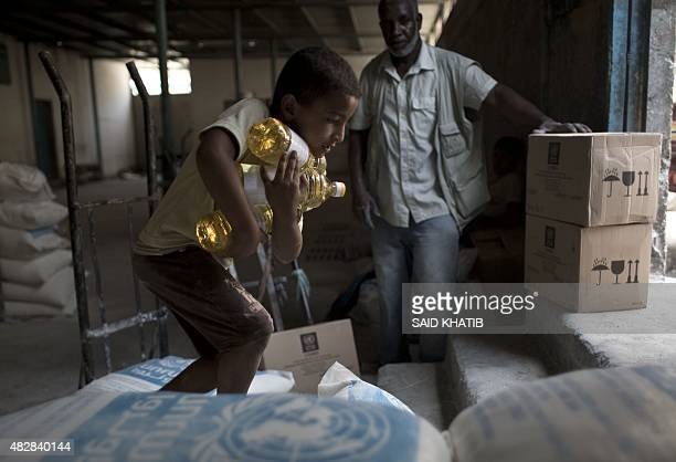 A Palestinian boy carries a bottles of oil distributed at an aid distribution centre of the United Nations Relief and Works Agency in Rafah in the...