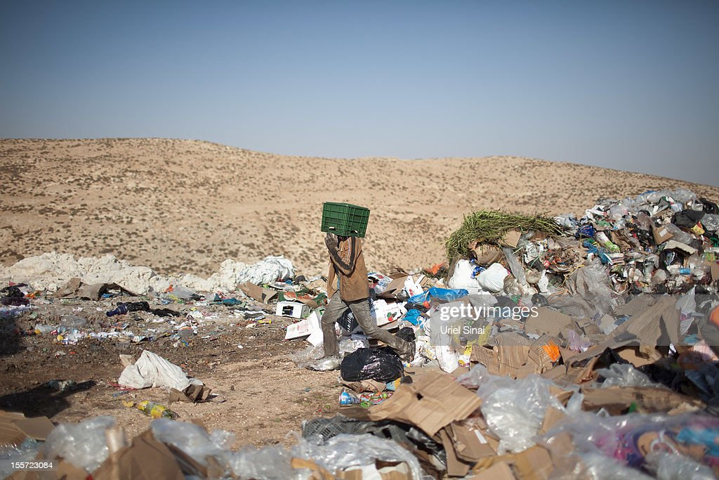 A Palestinian boy carries a case on his head as he sifts through a garbage dump on November 7, 2012 south of Hebron, West Bank. About 40 Palestinain men and children work at the West Bank garbage dump looking for clothing, metal and wood discarded, in large part, from the Jewish settelment in the region.