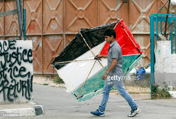 A Palestinian boy carries his kite in the colours of the national flag at the Aida Palestinian refugee camp near the Biblical city of Bethlehem in...