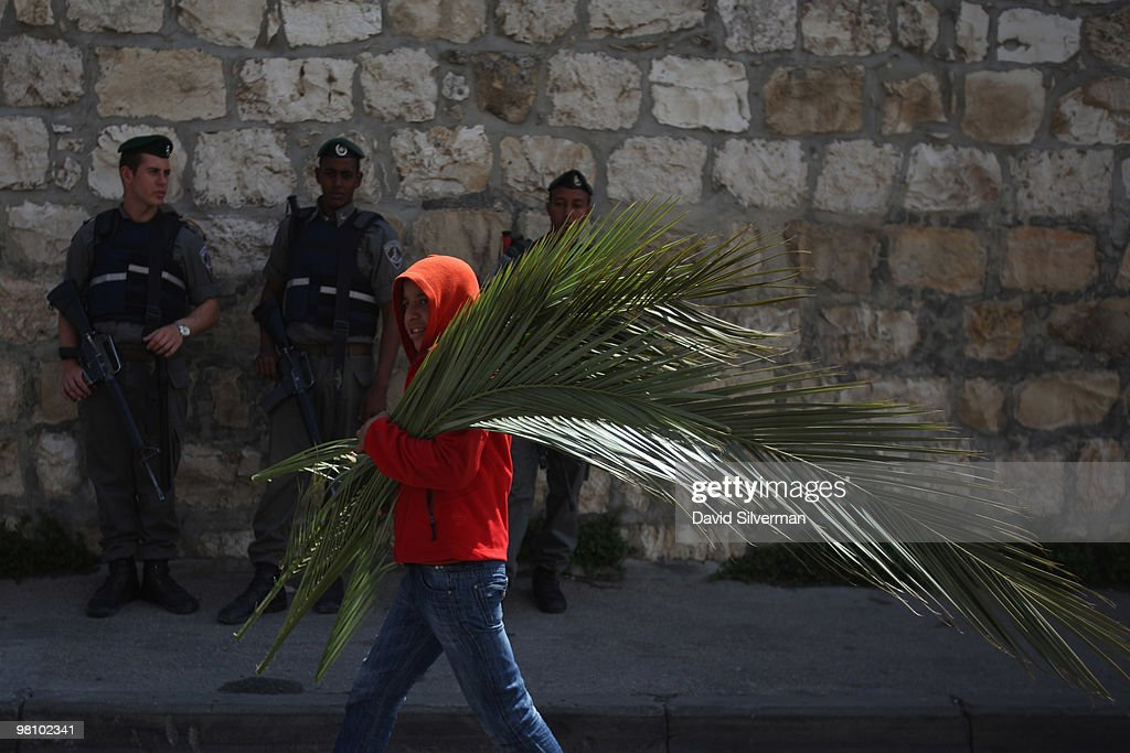 A Palestinian boy carries palm branches for sale to Christian pilgrims past Israeli police guarding the traditional Palm Sunday procession from the Mount of Olives to the Old City on March 28, 2010 in Jerusalem, Israel. Palm Sunday, which marks the start of Holy Week, is a landmark in the Christian calendar, marking the triumphant return of Jesus to Jerusalem the week before his death when a cheering crowd greeted him waving palm leaves.