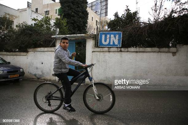 A Palestinian boy cycles past a United Nations' run health centre in the Qalandia refugee camp near Ramallah in the West Bank on January 17 2018...
