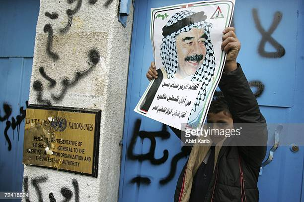 Palestinian boy displays an image of former Iraqi dictator Saddam Hussein outside UN headquarters during a rally in support of Saddam November 6 2006...