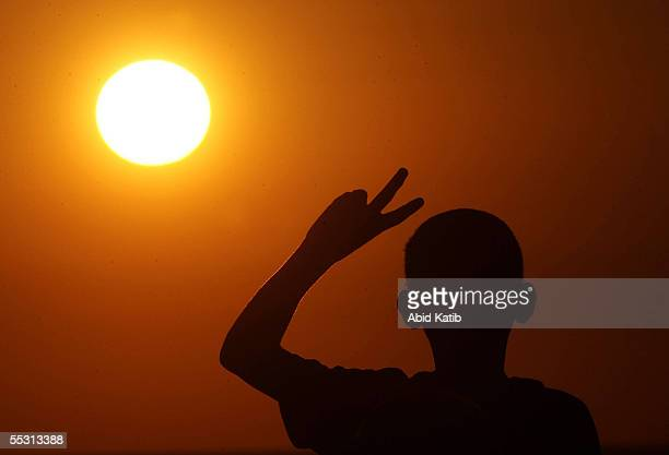 Palestinian boy gestures a Vsign as he looks at an Israeli tank open fire while guarding the border of the vacant Jewish settlement of Neve Dekalim...