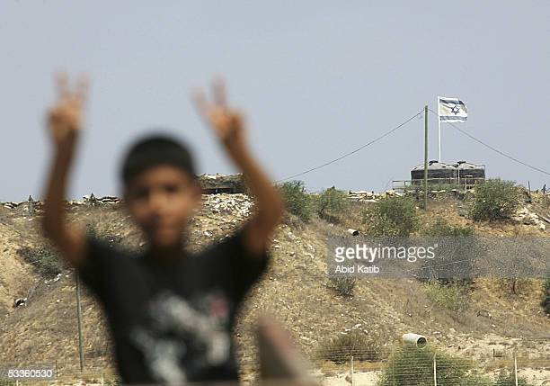 Palestinian boy gestures in front the Jewish settlement of Rafiah Yam during early celebrations of Israel's imminent pull out from Gaza, August 11 in...