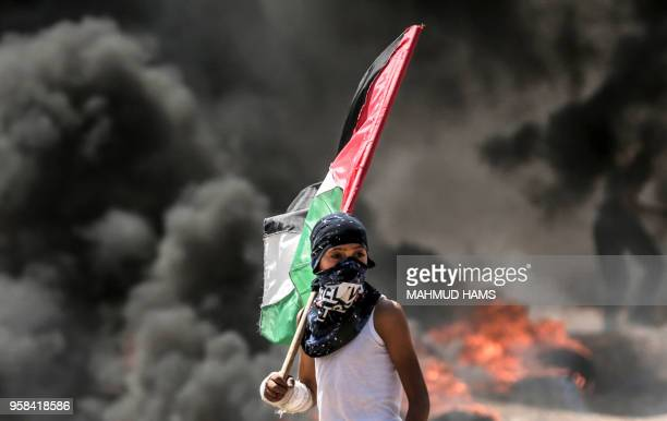 Palestinian boy holding his national flag looks at clashes with Israeli security forces near the border between the Gaza Strip and Israel east of...
