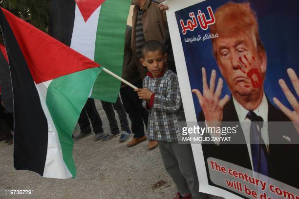A Palestinian boy holding his national flag stares at an image of US President Donald Trump during a demonstartion in the Rashidiyah camp near...