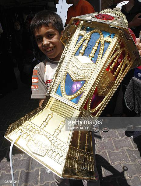 A Palestinian boy holds a giant lantern to be used during the Muslim holy month of Ramadan at a market in Rafah southern Gaza Strip on August 7 2010...