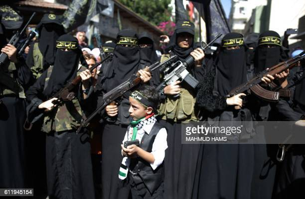 A Palestinian boy holds a gun in front of women from the Islamic Jihad Movement as they flash their weapons during a demonstration marking the first...