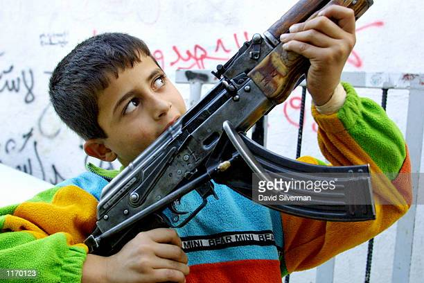 Palestinian boy holds a gunman's AK47 assault rifle during a round of fighting with Israeli soldiers October 26 2001 in the alAzzar refugee camp...