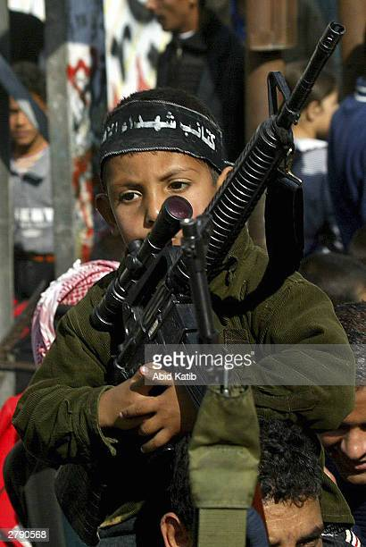 Palestinian boy holds a mock gun as the Al-Aqsa Martyrs Brigades, a militant group linked to Palestinian leader Yasser Arafat's Fatah movement, march...