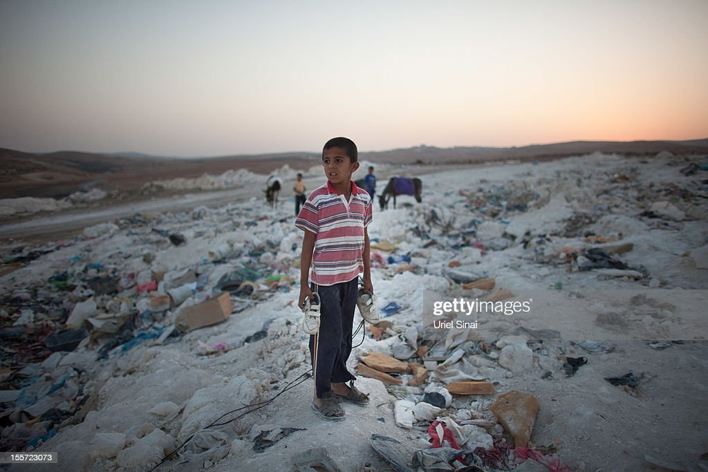 A Palestinian boy holds a pair of shoes he found while sifting through a garbage dump on November 7, 2012 south of Hebron, West Bank. About 40 Palestinain men and children work at the West Bank garbage dump looking for clothing, metal and wood discarded, in large part, from the Jewish settelment in the region.