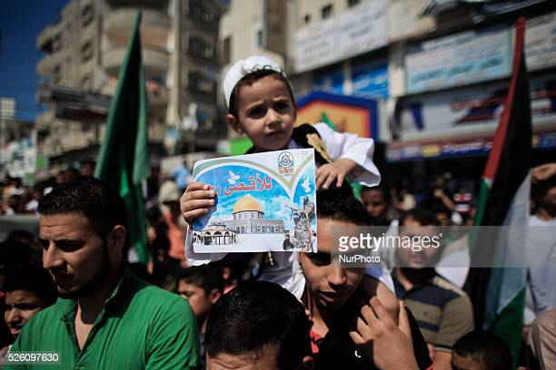 A Palestinian boy holds a picture for AlAqsa mosque during a rally marking 13th anniversary of the socalled AlAqsa uprising or 'Second Intifada' and...