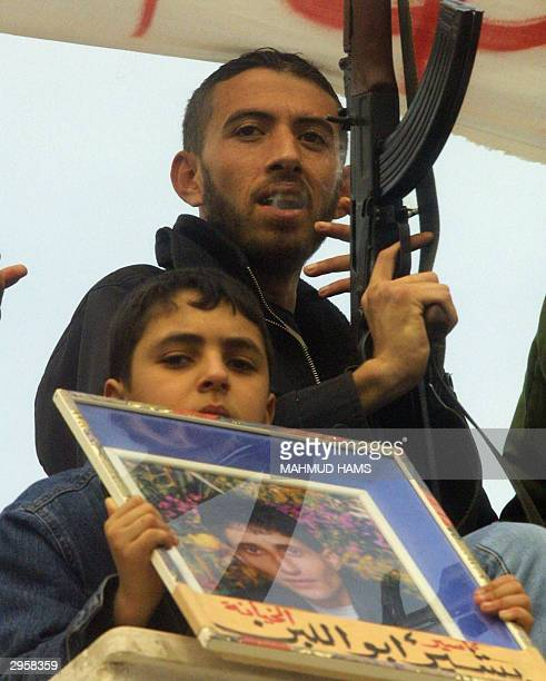 Palestinian boy holds a picture of Bashir Abu Laban a member of the Popular Resistance Committees who was arrested along with three others for the...