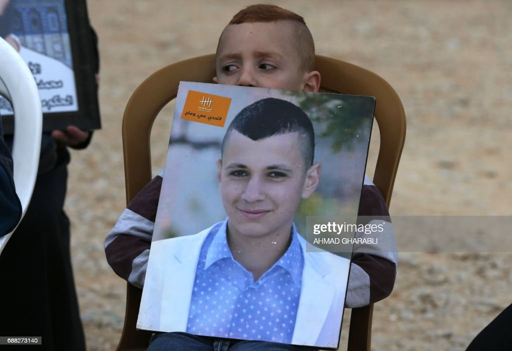 A Palestinian boy holds a portrait of a relative imprisoned in Israeli jails during a protest in front of the Red Cross offices in east Jerusalem on May 25, 2017, as hundreds of the detainees entered the second month of a hunger strike. Palestinian president Mahmud Abbas said he has asked the United States to mediate on a standoff between Israeli authorities and Palestinian prisoners on a weeks-long hunger strike. /