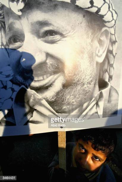Palestinian boy holds a poster of Palestinian leader Yasser Arafat during a march in support of Arafat on April 242004 in the Nussirat refugee camp...