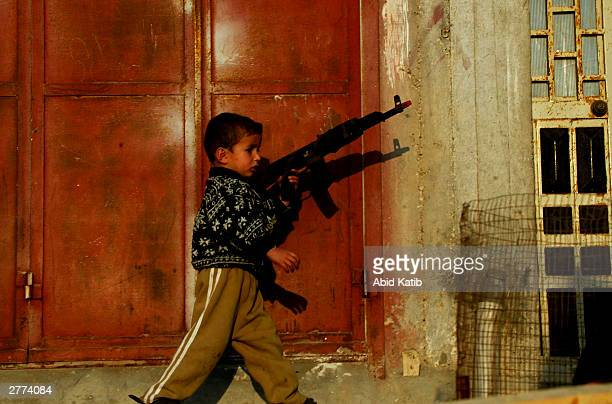 Palestinian boy holds a toy gun while protesters attend a demonstration against the Geneva Accord by different groups on December 1, 2003 in the...