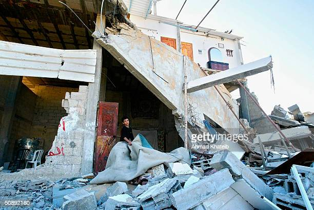 Palestinian boy inspects the rubble of his demolished house after Israeli troops pulled out of Tell alSultan neighbourhood on May 24 2004 in the...