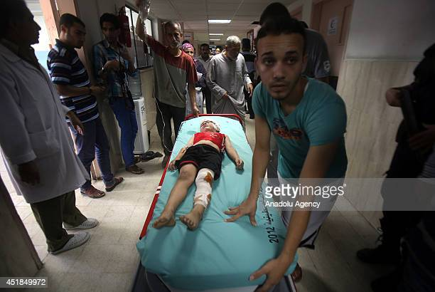 Palestinian boy is carried on a stretcher inside a hospital after he was injured in an Israeli airstrike in Khan Younis southern Gaza Strip on July 8...