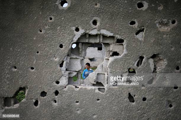 Palestinian boy is seen through a bullet riddled wall from a building which was destroyed during the 50day war between Israel and Hamas militants in...