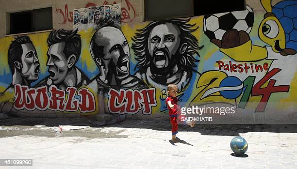 A Palestinian boy kicks a ball in front of graffiti wall murals depicting football players Portugal's Cristiano Ronaldo Argentina's Lionel Messi...