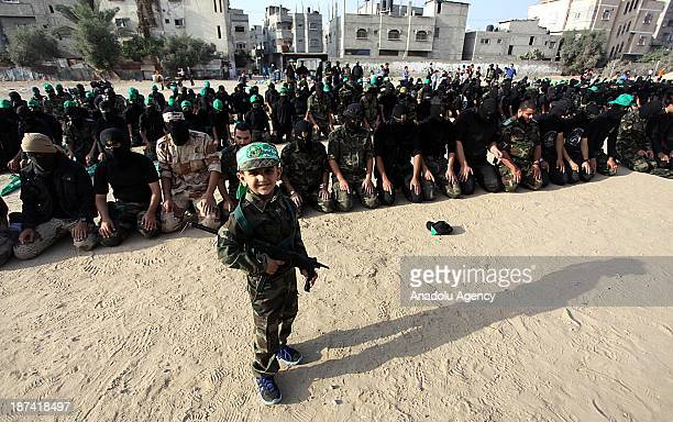 Palestinian boy looks as members of the Ezzeddin al-Qassam, the military wing of Hamas, perform prayer during an anti-Israel protest on the first...