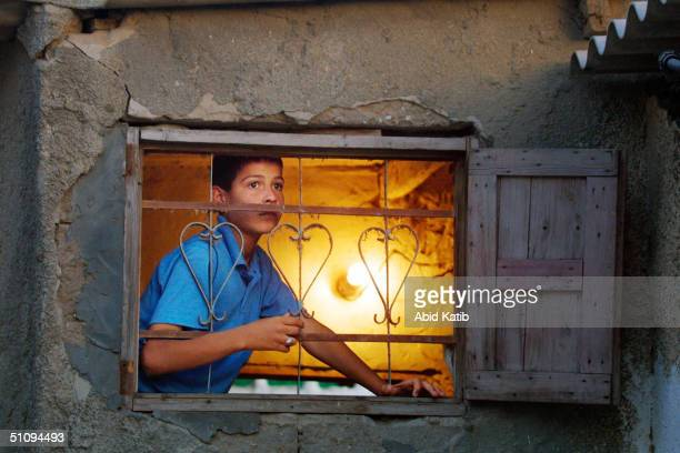 Palestinian Boy Looks From A Window Of His House During Clashes Between Israeli Troops And Palestinians May 29, 2002 In The Rafah Refugee Camp, Near...