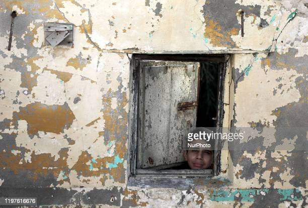 Palestinian boy looks from out the window of a house at al-Shati camp for Palestinian Refugees in Gaza City on January 30, 2020. Palestinians have...