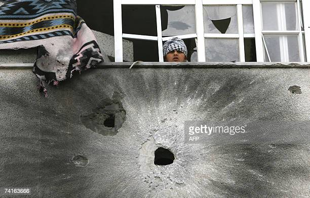 Palestinian boy looks from the window, just above the pockmarked wall following overnight factional clashes between President Mahmud Abbas's secular...