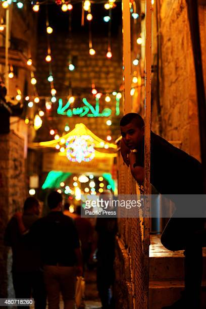 Palestinian boy looks on as people go to and back from Al Aqsa Mosque in the old city of Eastern Jerusalem during the night of Laylat Al Qadr In the...