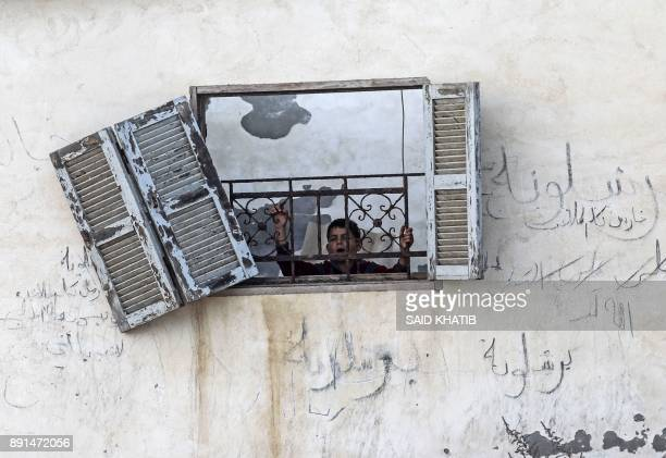 Palestinian boy looks out from the window of his house that was damaged in an Israeli airstrike on a nearby Hamas base in Khan Yunis town in the...