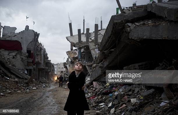 Palestinian boy looks up during a rain storm while walking through a neighbourhood destroyed during the 50 day conflict between Israel and Hamas, in...