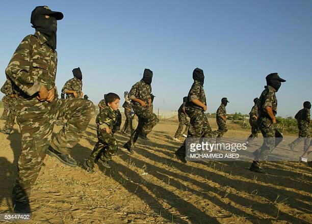 Palestinian boy marches with masked members of the radical Palestinian group Islamic Jihad during a military training session at the Rafah refugee...