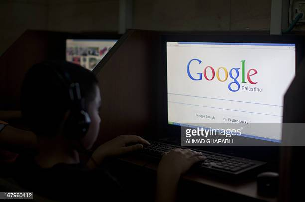A Palestinian boy opens the Palestinian homepage of Google's search engine reading 'Palestine' at an internet cafe in east Jerusalem on May 3 2013...