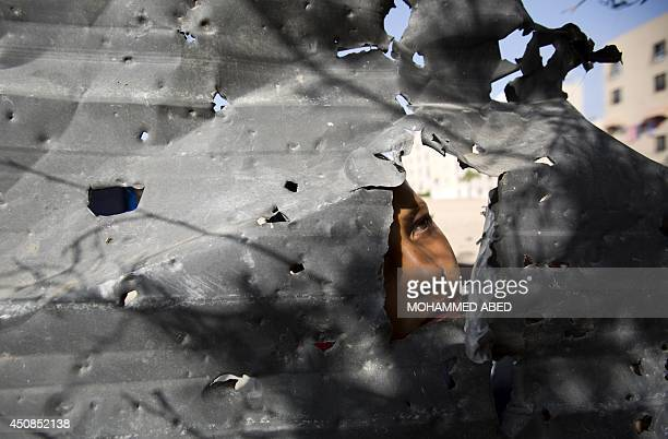 A Palestinian boy pears from behind a shrapnel riddled metal piece following an Israeli air strike in the Gaza Strip's northern Beit Lahia town on...