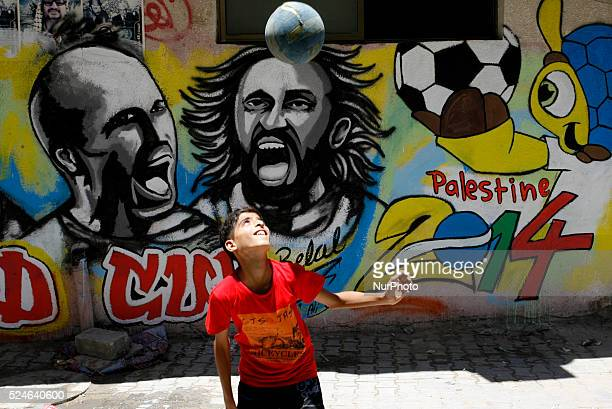 A Palestinian boy plays a ball in front of graffiti wall murals depicting football players the participants at 2014 World Cup Brazil Netherlands'...
