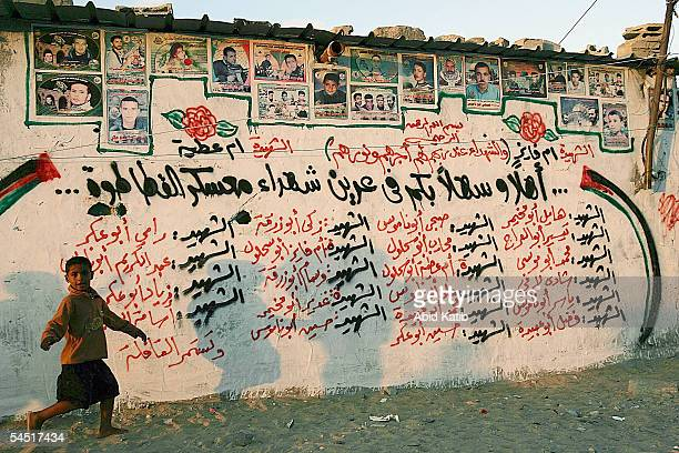 A palestinian boy plays in front a wall covered with names and posters of their countrymen martyrs who were killed by Israeli Army during the...