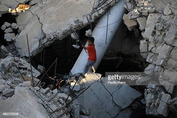 Palestinian boy plays in the rubble of mosque destroyed during the 50day war between Israel and Hamas militants in the summer of 2014 in the village...