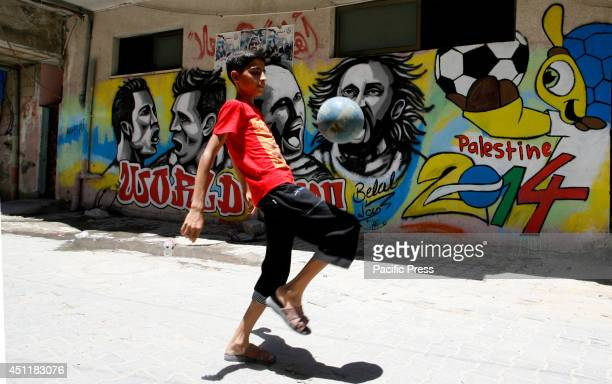 Palestinian boy plays with a ball in front of a graffiti wall in the Khan Yunis refugee camp in the southern Gaza Strip depicting football players...